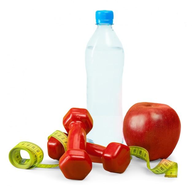 Mancuernas, manzana y cinta métrica