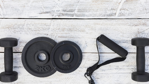 Mancuernas; placas de peso y correa de fitness sobre fondo blanco con textura de madera