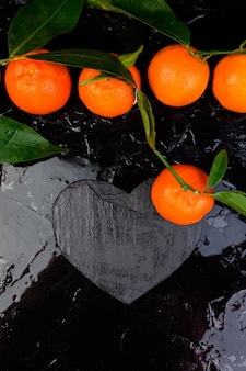 Mandarina alrededor con pizarra negra en forma de corazón.