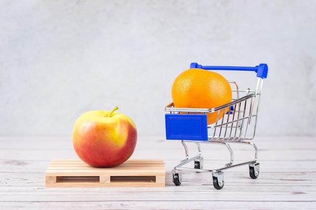 Mandarina en el carrito de la compra y una manzana en un palet, el concepto del almacén