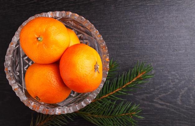 Mandarina en una cesta de metal con una rama de un árbol de navidad sobre un fondo negro