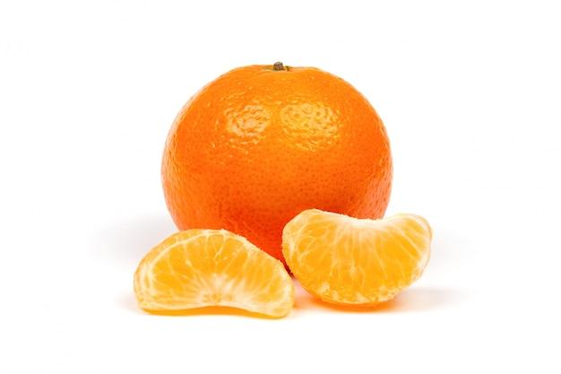 Mandarina madura en cáscara y rodajas de mandarina peladas primer plano aislado