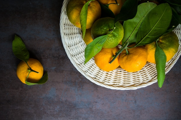 Mandarina madura con hojas verdes