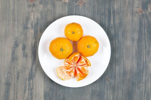 Mandarina pelada con mandarinas enteras en la placa blanca.