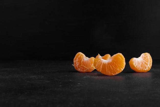 Mandarina pelada y en rodajas sobre fondo negro, vista de perfil.