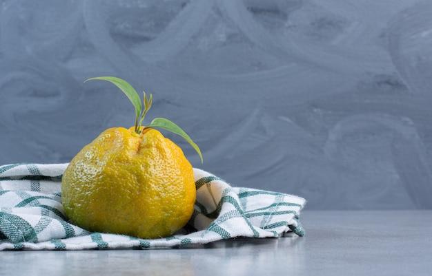 Mandarina sola sobre una toalla sobre fondo de mármol.