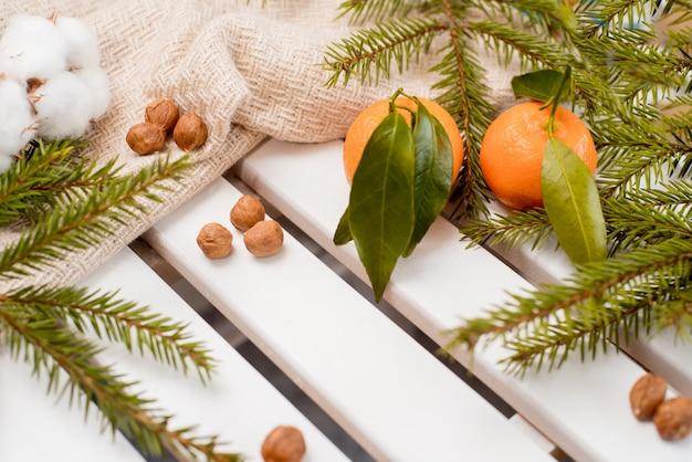 Mandarinas en canasta con rama de árbol