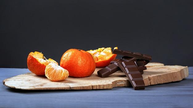 Mandarinas con chocolate negro sobre soporte de madera sobre un fondo gris oscuro.