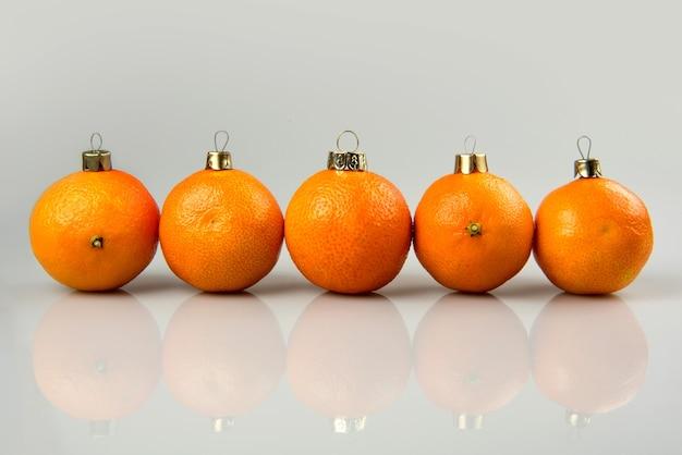 Mandarinas como bola de navidad en navidad y año nuevo. diseño de decoración de concepto de vacaciones de frutas de juguete de abeto de tradición rusa en vacaciones.