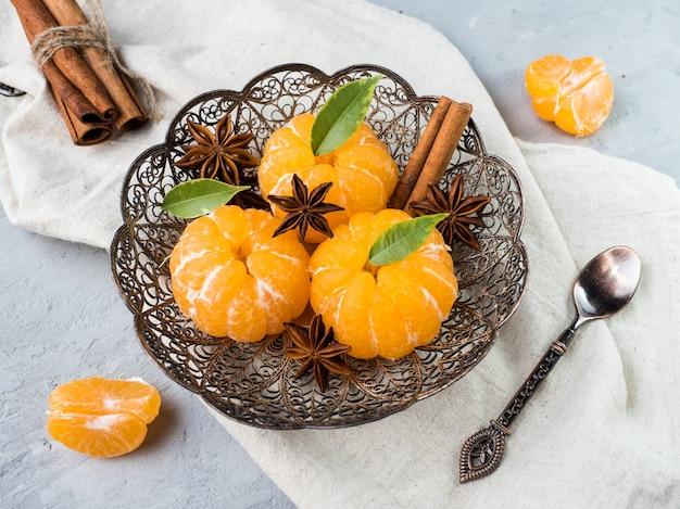 Mandarinas frescas en un plato con ramas de abeto, anís estrellado, canela en gris