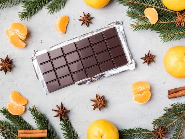 Mandarinas frescas con ramas de árbol de navidad, anís estrellado, canela de chocolate sobre hormigón gris, espacio de copia