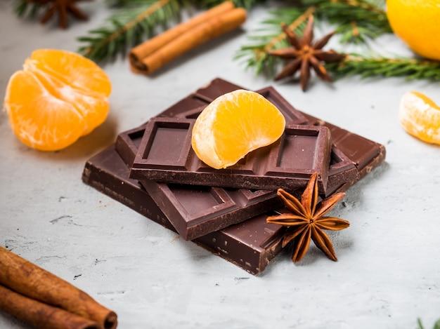 Mandarinas frescas con ramas de árbol de navidad, anís estrellado, canela de chocolate sobre hormigón gris