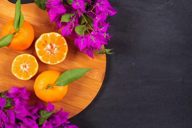 Mandarinas frescas en tabla de cortar de madera con flores de color púrpura sobre superficie negra con espacio de copia