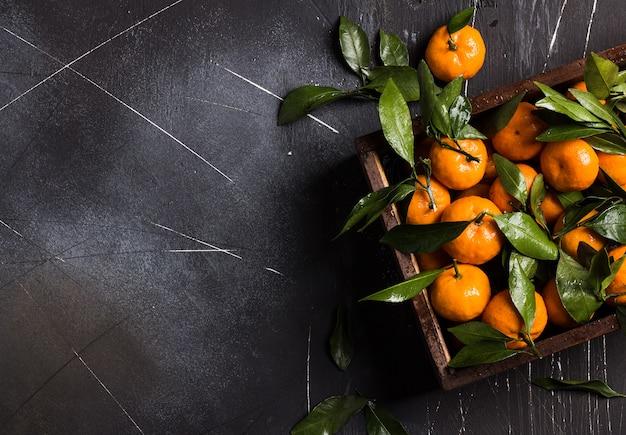 Mandarinas con hojas verdes en caja de madera en oscuridad