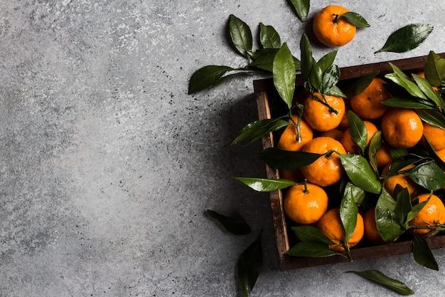 Mandarinas con hojas verdes en caja de madera sobre luz