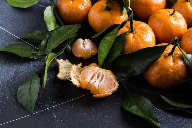 Mandarinas con hojas verdes de cerca en la oscuridad