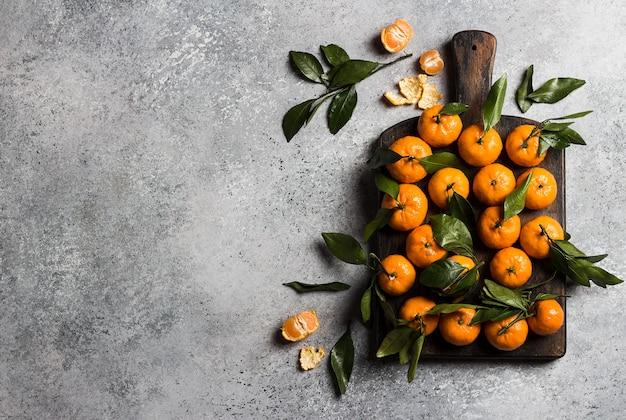 Mandarinas con hojas verdes en tablero de madera en luz