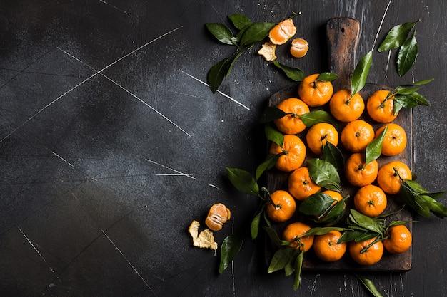 Mandarinas con hojas verdes en tablero de madera en la oscuridad