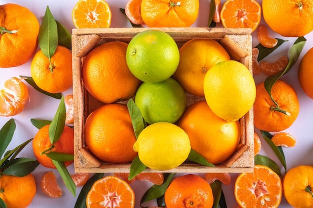 Mandarinas limones y frutas naranjas en caja de madera sobre superficie blanca