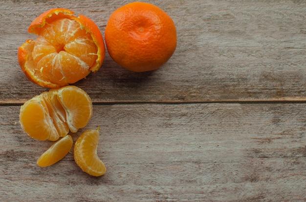 Mandarinas, mandarina pelada y rodajas de mandarina en una mesa de madera blanca. copia espacio