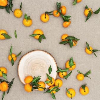 Mandarinas (naranjas, clementinas) con hojas verdes sobre fondo de tela de saco.