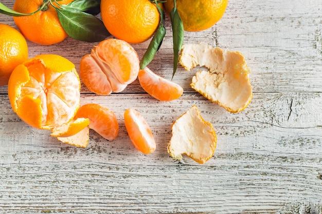 Mandarinas naranjas con hojas verdes en madera blanca