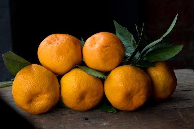 Mandarinas naranjas con hojas verdes.