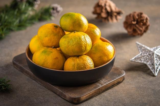 Mandarinas o mandarinas y rodajas maduras en un tazón de bambú sobre tabla de madera, junto a la rama de un árbol de navidad, conos y estrellas