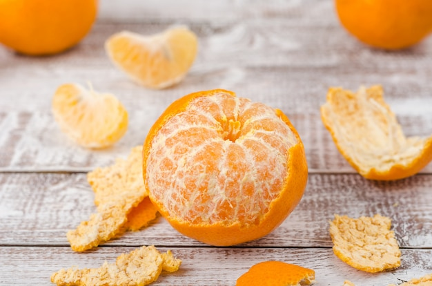 Mandarinas peladas sobre fondo de madera