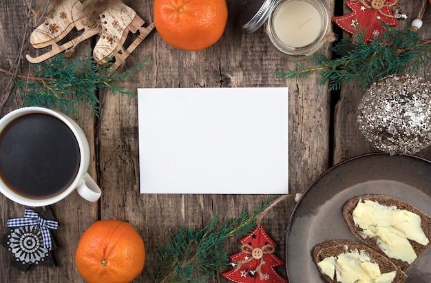 Mandarinas, ramas de coníferas, árboles de navidad, una taza de café y bocadillos en una mesa de madera natural.