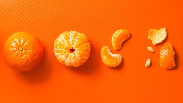 Mandarinas sobre un fondo naranja, cuñas y cáscaras peladas enteras, banner plano laico