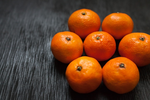 Mandarinas sobre un fondo negro. mucha fruta fresca - mandarinas.
