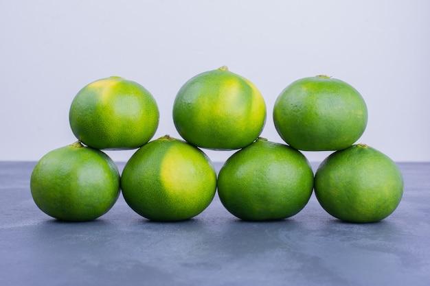 Mandarinas verdes sobre azul.