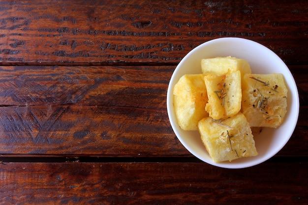 Mandioca hervida y frita (mandioca) en un tazón de cerámica en una mesa de madera rústica en restaurante