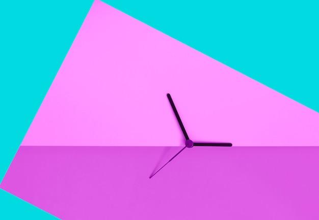 Las manecillas del reloj en rosa ácido con turquesa coloure bloquean el fondo. concepto de horario de verano. cambio estacional de tiempo. concepto de tiempo. copia espacio