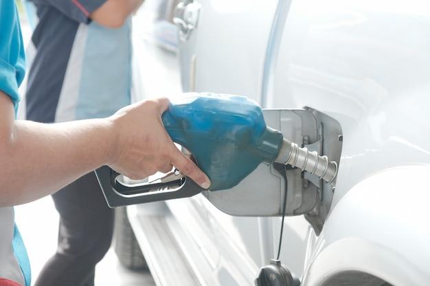 Manejar la boquilla de combustible para repostar. instalación de carga de vehículos.