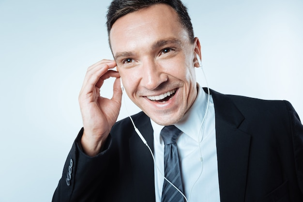 Manera de relajarse. hombre encantado alegre feliz sonriendo y sosteniendo auriculares mientras disfruta de su música
