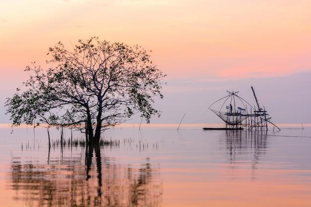 Manglares en el lago con red de inmersión cuadrada en la salida del sol en la aldea pakpra, phatthalung, tailandia