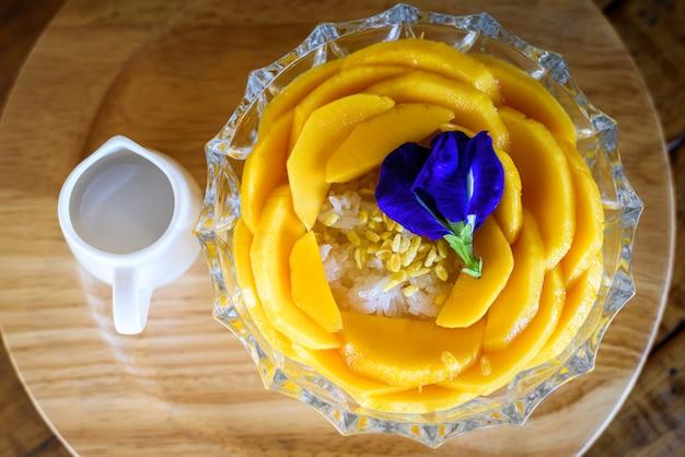 Mango arroz con leche de coco en la mesa de madera, popular postre tailandés tradicional