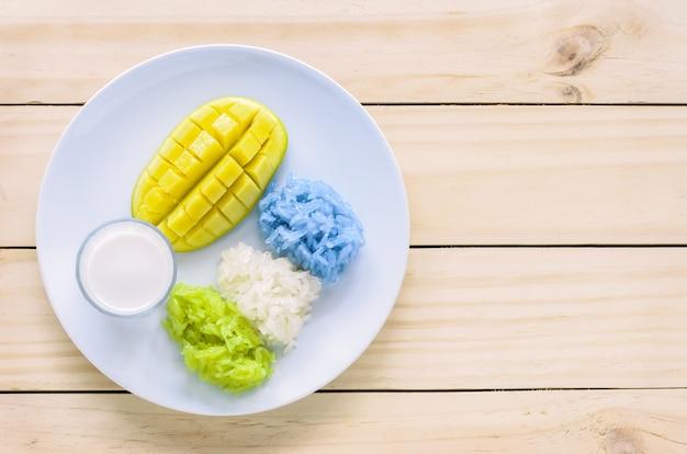 Mango y arroz pegajoso de color natural con leche de coco, postre tailandés
