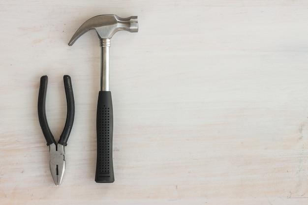 Mango de escombros de martillo de acero y alicates en madera blanca