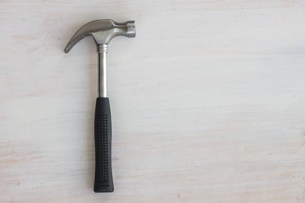 Mango de escombros de martillo de acero sobre madera blanca