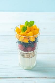Mango, frambuesa y arándano caseros con yogur y granola - estilo de comida saludable