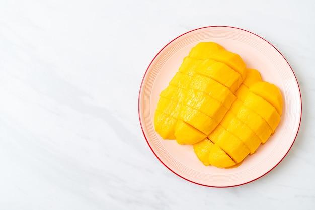 Mango fresco y dorado cortado en un plato