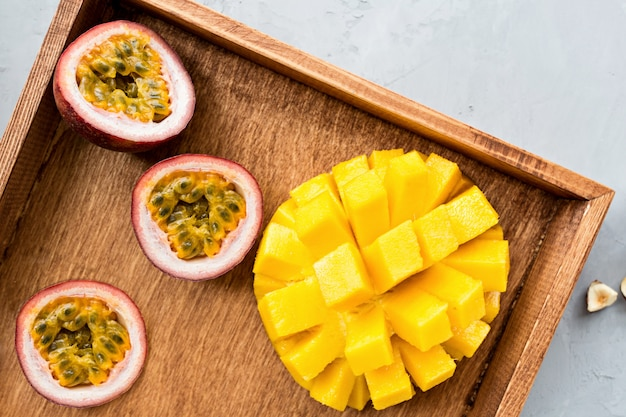 Mango fresco y frutas de la pasión en placa de madera.
