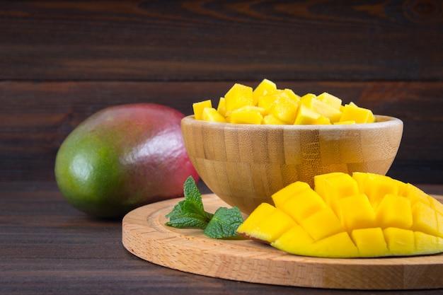 Mango de la fruta tropical en una placa en un fondo de madera, entero o cortado.
