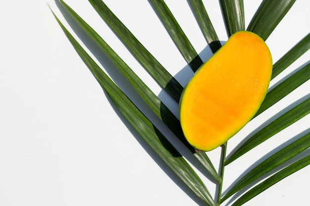 Mango en hojas de palmeras tropicales sobre superficie blanca