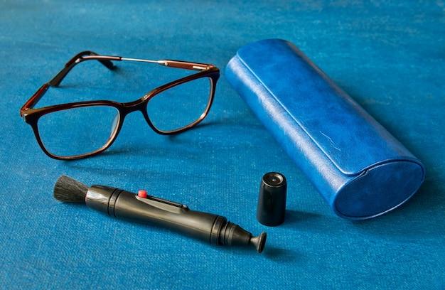 Mango de limpieza para óptica, gafas y estuche de gafas en el espacio azul, de cerca, poca profundidad de nitidez