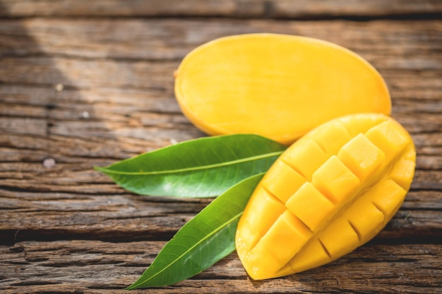 Mango maduro cortado en tablero arbolado con hojas verdes.