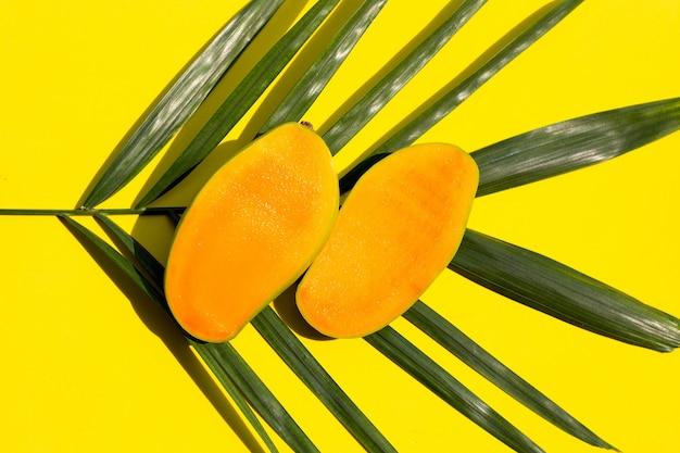 Mango maduro medio cortado en hojas de palmeras tropicales sobre superficie amarilla